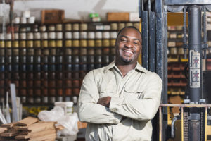 A smiling, confident, African American man working in a printing factory.  He is standing with arms crossed in the storage warehouse, next to a forklift.  Containers of ink line the shelves in the background.