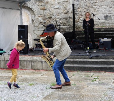 A dancing 6 year old being serenaded by the saxophonist