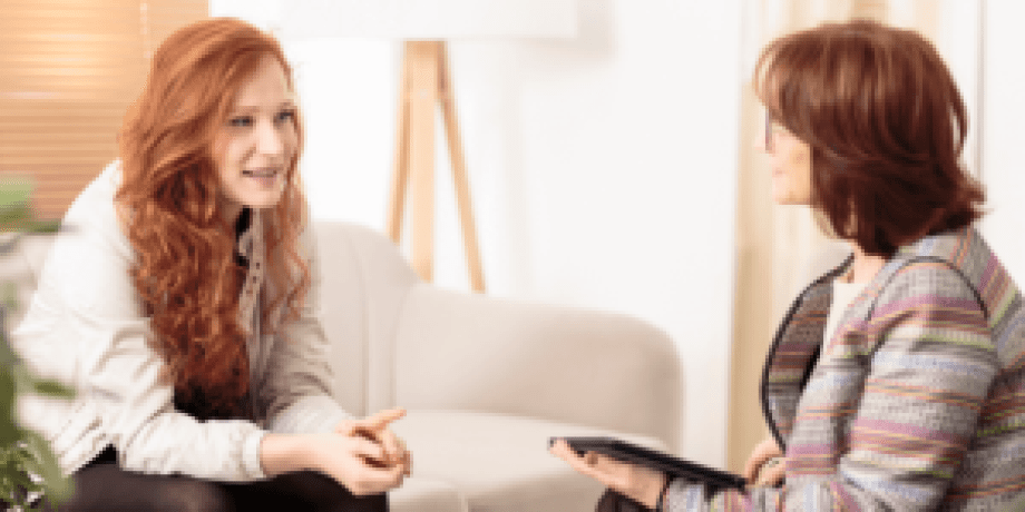Red headed girl consulting with brunette female doctor