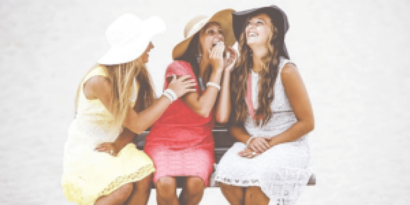 three girls sharing a secret