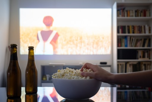Person Eating Popcorn in Home Theater