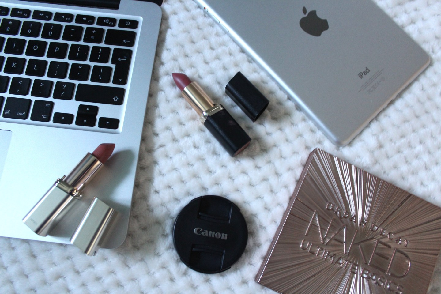 A photo of a macbook, ipad mini and some makeup
