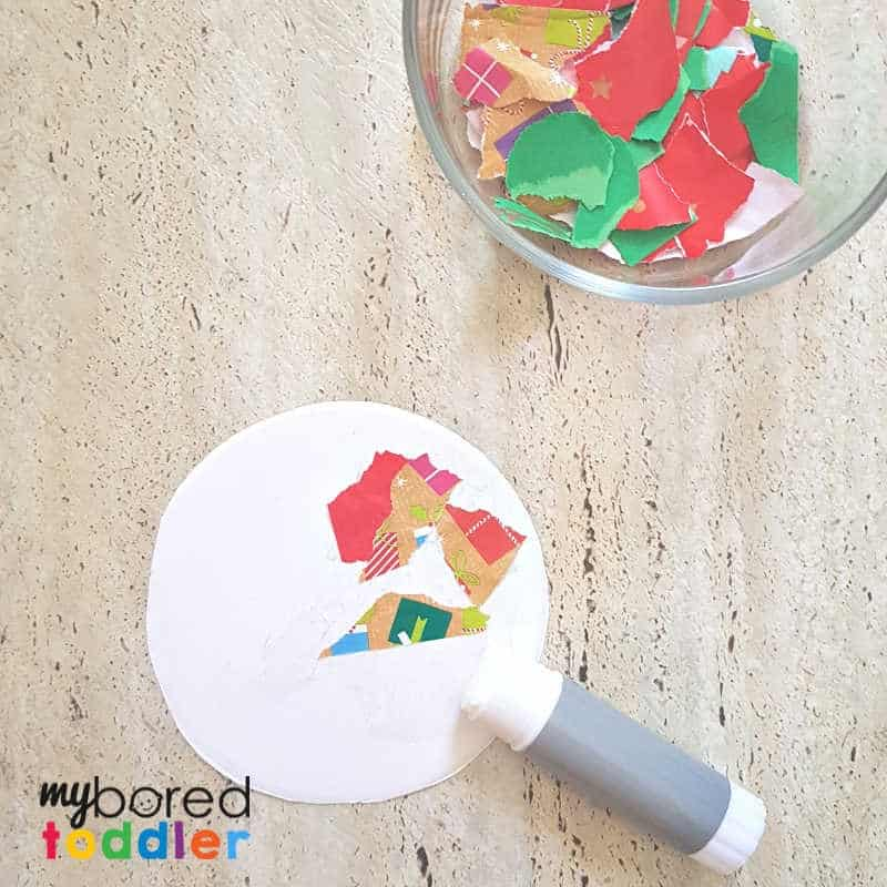easy christmas ornament for toddler gluing the paper on