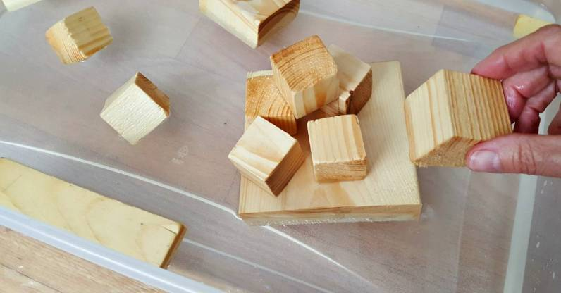 Stack small wood blocks in a water play activity for toddlers