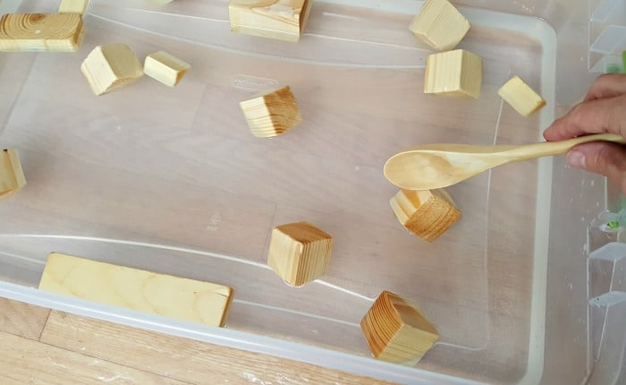 Stir small blocks in water play activity