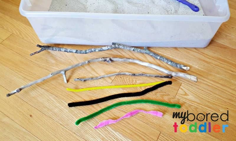 Sand in the sensory bin with pipe cleaner caterpillars and small twigs1