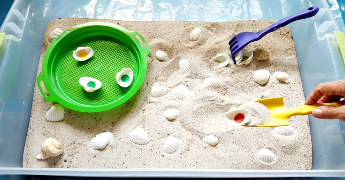 Digging for seashells in the sensory bin