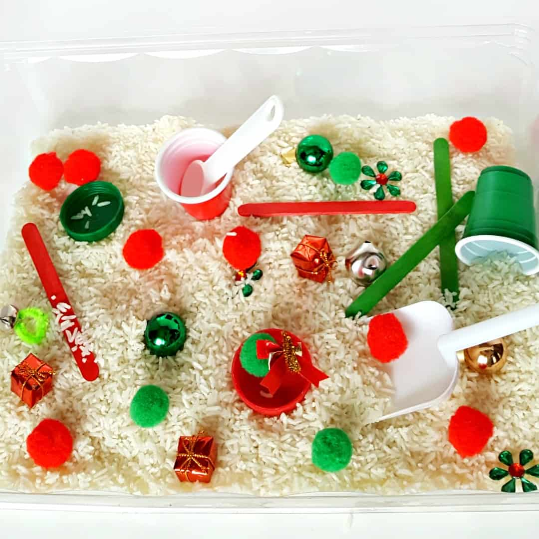 Toddler holiday sensory bin with rice and pompoms
