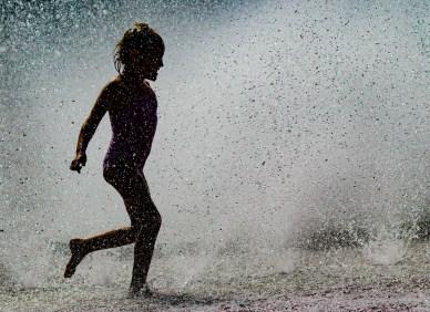 silhouette of little girl in fountain