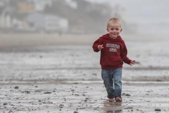little boy walking barefoot in sand on beach