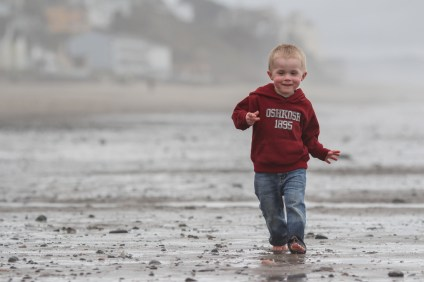 little boy walking barefoot in sand on beach