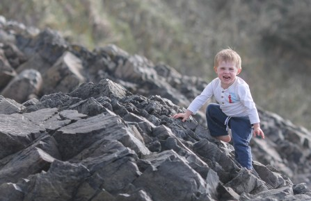 little boy climbing on rocks