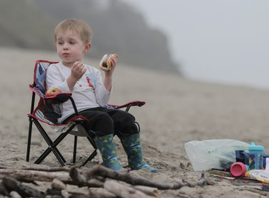 little boy in chair eating hot dog on the beach