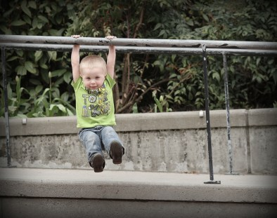 little kid hanging on railing