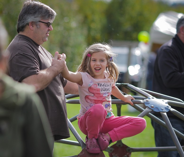 dad helping daughter off play structure