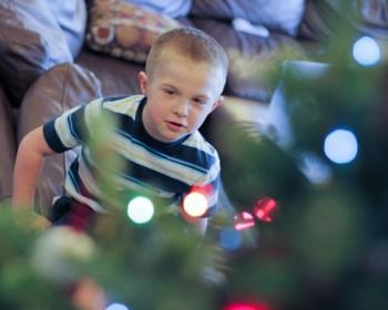 little boy decorating Christmas tree