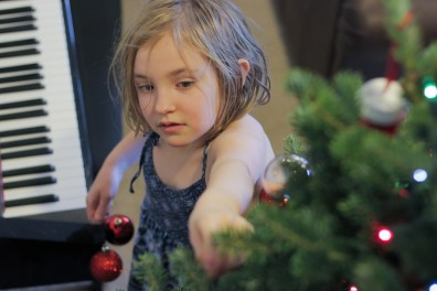 little girl decorating Christmas tree