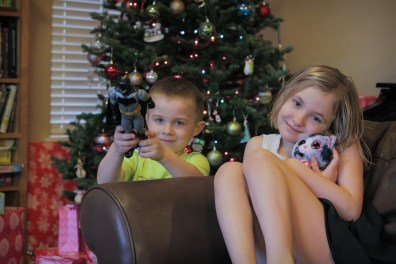 little kids brother and sister showing off Christmas presents
