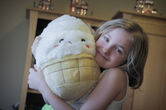 little girl holding a stuff animal Christmas present