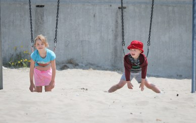 brother and sister on swings at beach