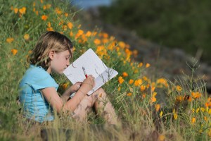 little girl sitting flowers writing in journal