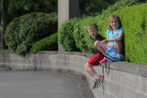 brother and sister sitting on a wall