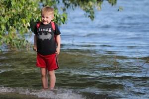 little boy standing in water
