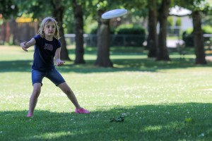 little girl throwing frisbee
