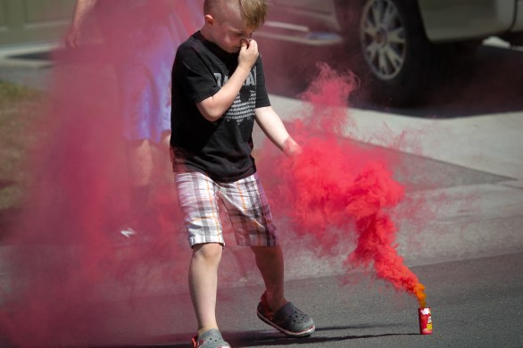 little boy running through red smoke bomb