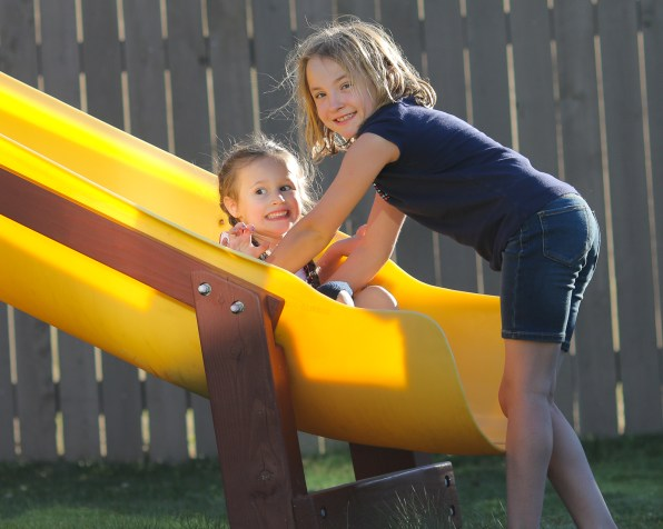 two little girls on yellow slide