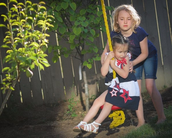 two little girls playing on swing