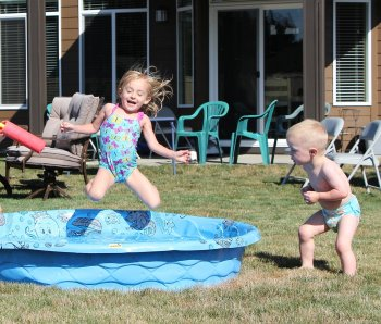little girl flying through the air into kiddie pool