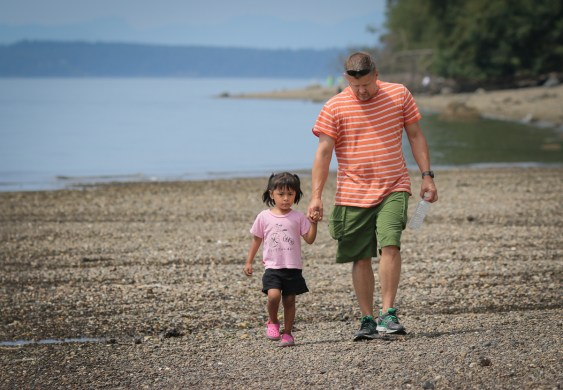 daddy and daughter walking by edge of ocean