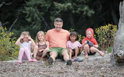 little friends sitting on log on beach