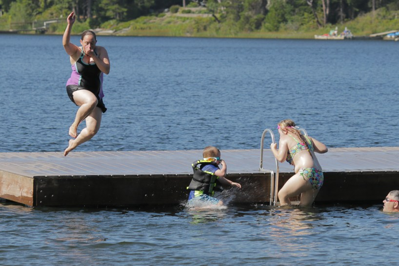 Mom and son jumping off dock
