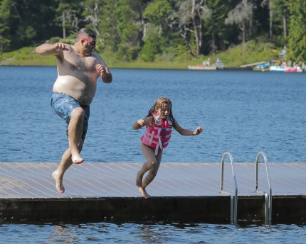 dad and daughter jumping off dock