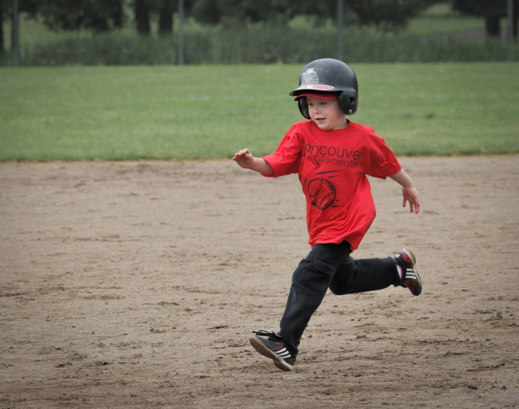 little boy running bases