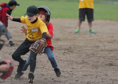 girl running bases crashing into someone