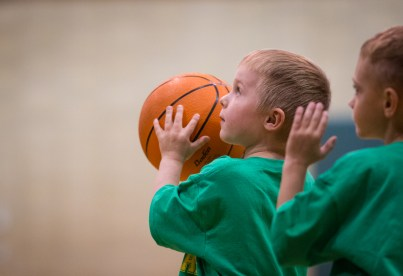 little boy shooting basketball