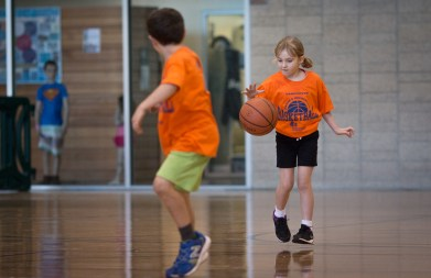 little girl dribbling basketball