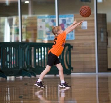 little girl passing basketball