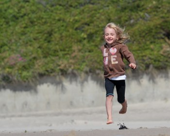 little girl running through sand