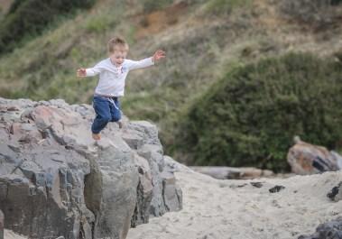 boy jumping off high rock
