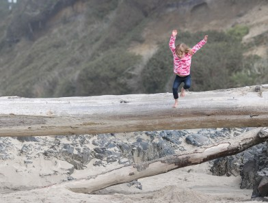 girl jumping off high log