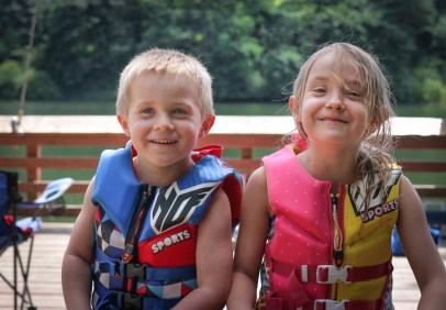 brother and sister smiling in life jackets