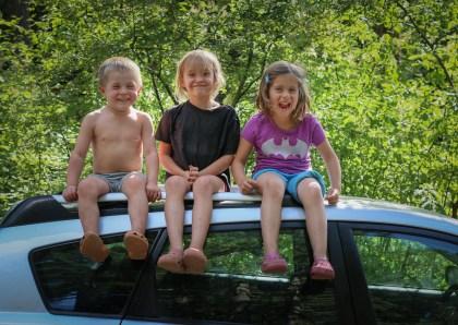 three little kids sitting on top of car