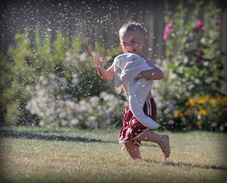 little boy running through sprinkler in back yard