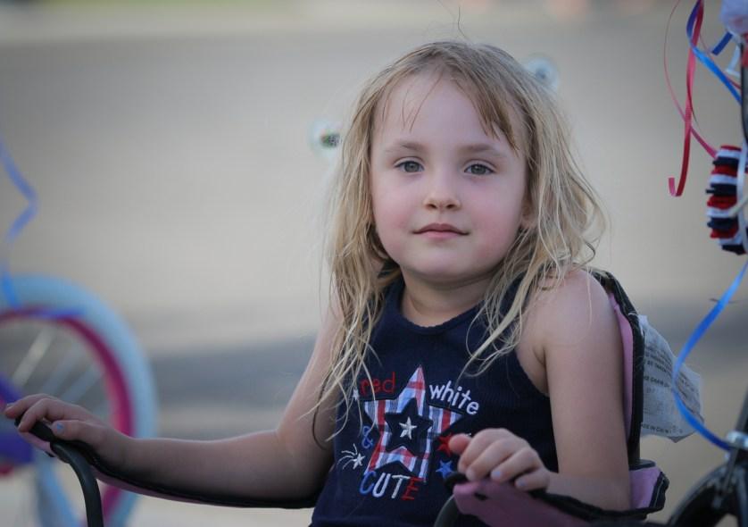 little girl sitting in chair outside