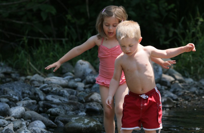 little boy walking in river