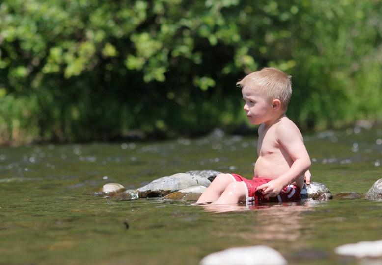 little boy sitting in river